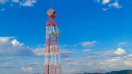 LTE, GSM, 2G, 3G, 4G, 5G tower of cellular communication. Telecommunication tower against the blue sky with clouds
