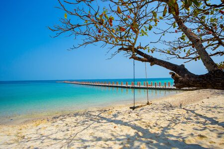 The sea in summer. This image has just been taken from the seaside view on the island in Thailand recently. In the picture there is a large branch that spreads the shade on the sand and the sea below Reklamní fotografie