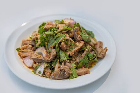 Spicy minced pork salad or Ground pork salad (Laab) is a Thai food for health consists of pork ground rice chili lemon onion and herb mixed in plate on a wood table at Thai street food