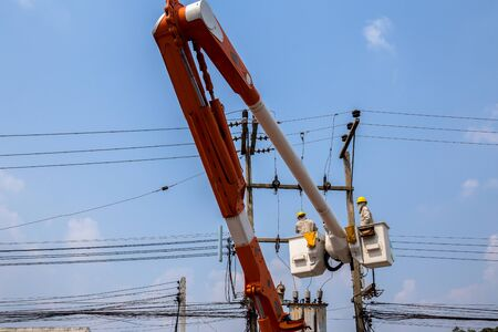 Electric technical in lift bucket during installation of metal pole with street lamp Stock fotó