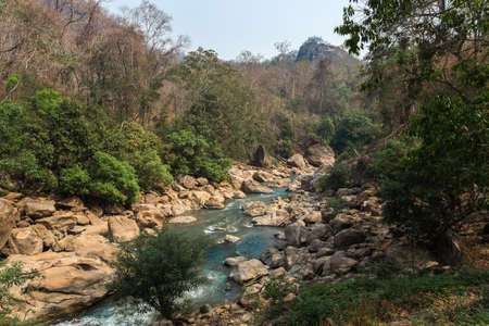 Close up of river stream flowing down over the grey stones. Stock footage. Fast and cold brook with clear water flowing on rocky area 免版税图像