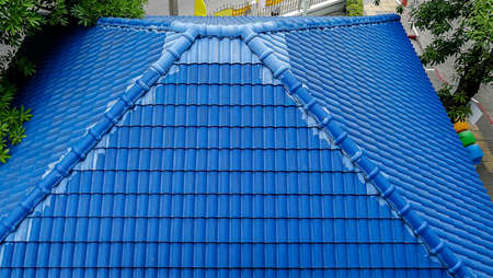 A roof of a house or cottage made of blue metal tiles with drains, slopes and chimney against the blue sky