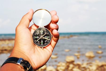 La mano del hombre con una brújula negro y plata en una playa Foto de archivo