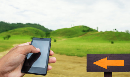 forsale: Hand hold and touch screen smart phone, tablet,cellphone over green mountain blur. Stock Photo