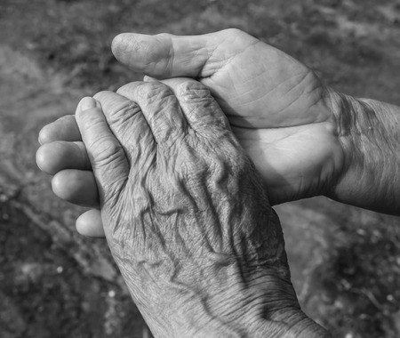 human relations: Close-up of elderly couple holding hands black and white.
