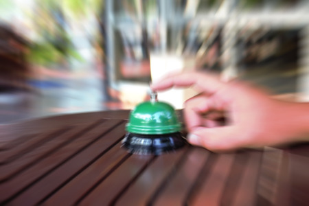 attract attention: Hand man push hotel bell motion blur.