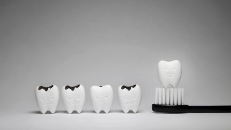 Tooth model in happy emotion and black toothbrush, if brush the teeth, teeth will good healthy Stok Fotoğraf