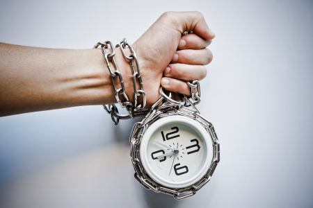 imprisonment: A hand chained with a clock