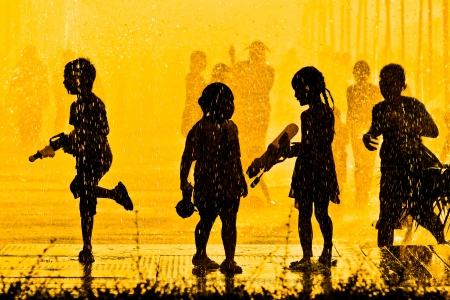songkran: children playing in water silhouette Stock Photo