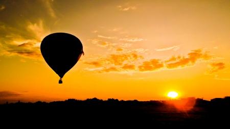 hot air ballon: balloon silhouette with sunrise Stock Photo