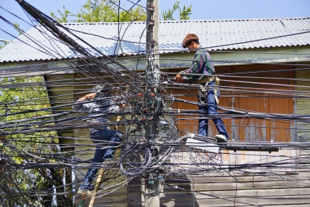 Ubon Ratchathani, Thailand - January 20, 2014  Two Thai electricians are fixing confusing electricity lines on a pole