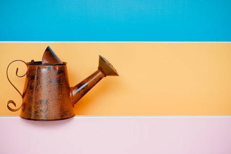 old and rusty watering can with colorful wood background photo