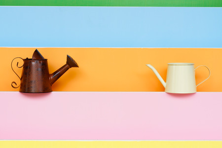 old and new watering can with colorful wood background  photo