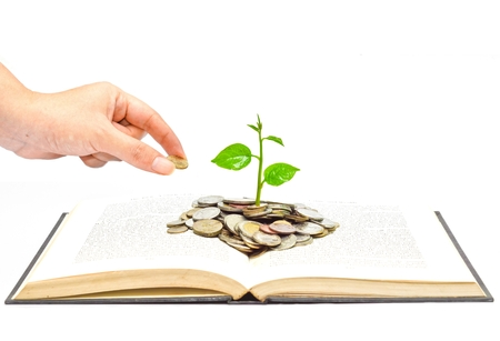 hand giving a golden coin to trees growing on coins over a book photo