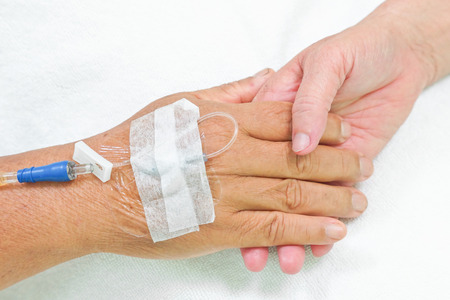 old hands holding each other with IV solution in a patient s hand