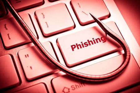 data theft: phishing   a fish hook on computer keyboard   computer crime   data theft   cyber crime