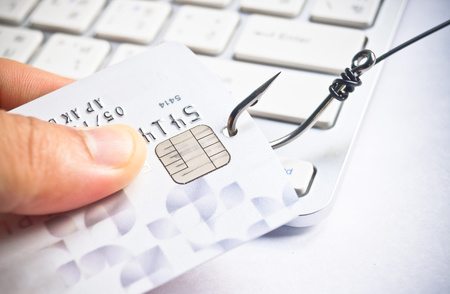 internet fraud: phishing - fish hook with a credit card on white computer keyboard