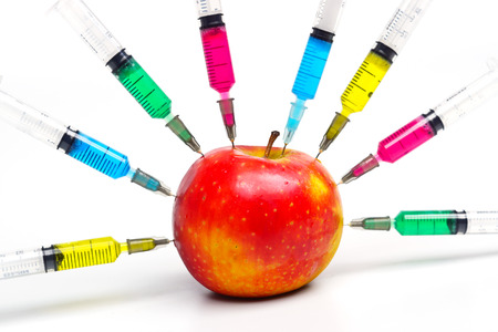 apple gmo: gmo apple surrounded by syringes