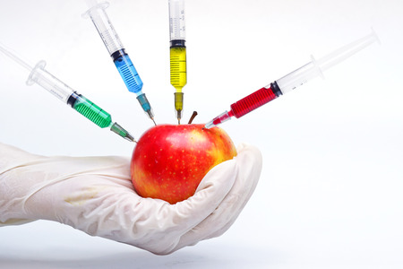 apple gmo: hand injecting chemical to apple - gmo fruit Stock Photo