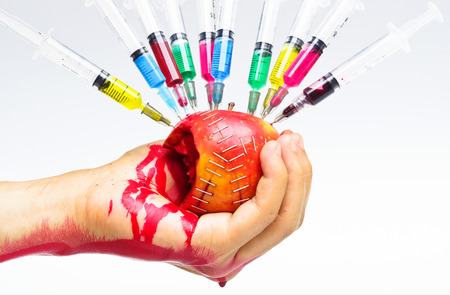hand holding gmo apple surrounded by syringe with blood drop - danger of consuming gmo fruit Stock Photo