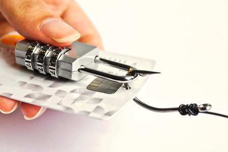 hand holding a security lock with password and fish hooks on credit cards - phishing protection concept photo