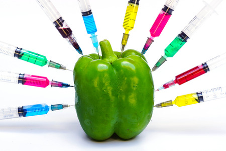 hand injecting gmo vegetable - sweet pepper surrounded by syringes with colorful chemicals photo