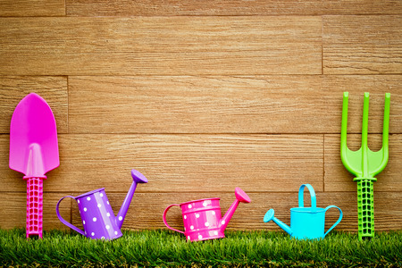 fork, shovel and rake on green grass with wood background - colorful gardening tools photo