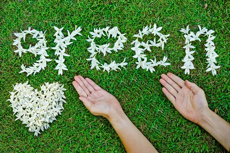 green: hands with white flowers arranged as a word go green with white heart Stock Photo