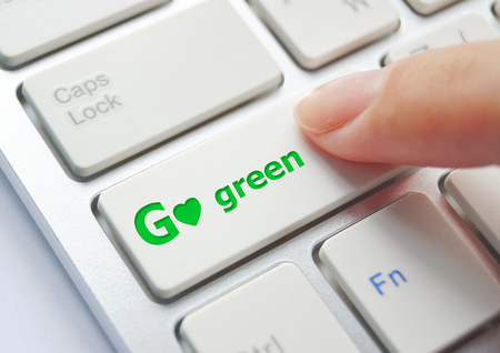 go green background: finger pressing go green button on keyboard background Stock Photo