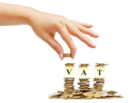 Hand Zahlung der Mehrwertsteuer (Value Added Tax) auf Stapel Goldmünzen mit isolierten Hintergrund