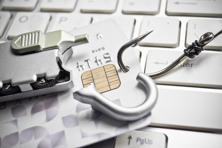 phishing - fish hook with a credit card and broken security lock on white computer keyboard photo