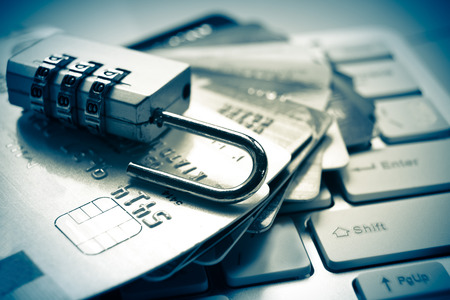 internet fraud: open security lock on credit cards with computer keyboard - credit card data theft