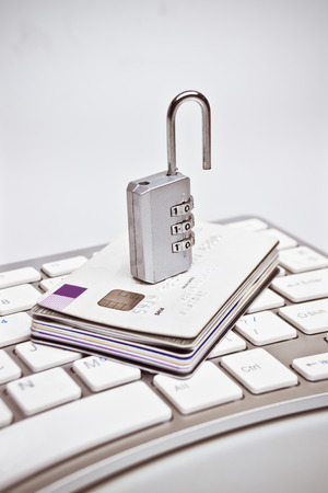 data theft: open security lock on credit cards with computer keyboard - credit card data theft
