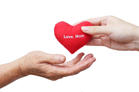take care of old mother - young female hand giving a red heart to old hand of a mother photo