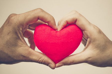 love hands: mans hand and womans hand holding a red heart Stock Photo