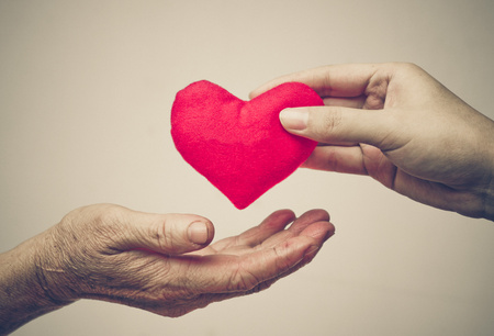 empatia: cuidar de madre - mano femenina joven que da un corazón rojo a la vieja mano de una madre