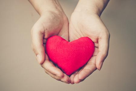 simbolo de la mujer: manos sosteniendo un coraz�n rojo