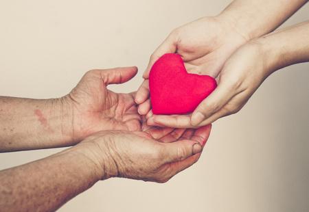 simbolo de la mujer: cuidar de madre - mano femenina joven que da un coraz�n rojo a la vieja mano de una madre