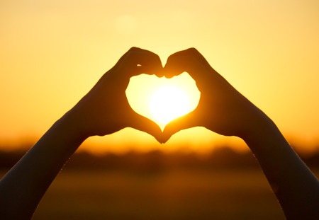 Hände bilden eine Herzform mit Sonnenuntergang Silhouette Standard-Bild - 33672314