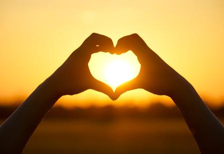 forme: mains formant une forme de coeur avec le coucher du soleil, silhouette