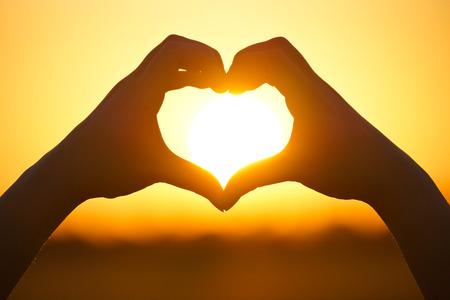 mãos que formam uma forma do coração com silhueta do sol