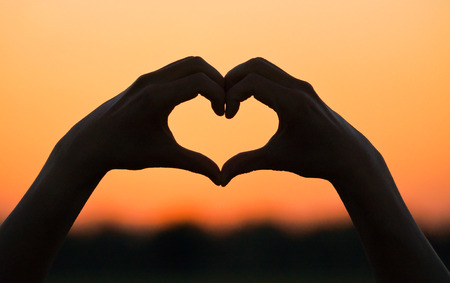 hands forming a heart shape with sunset silhouette photo