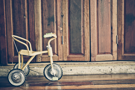 tricycle: yellow tricycle for baby with wood background
