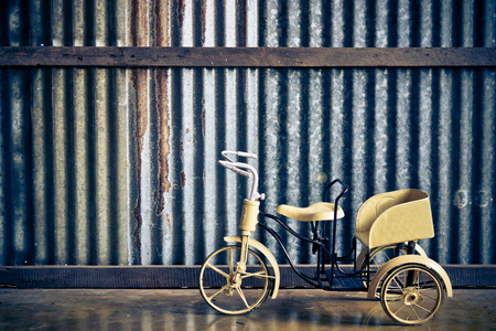 yellow tricycle for baby with wood background photo