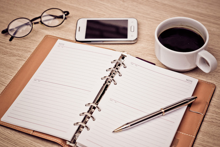 surface of a wooden table with notebook, smartphone, eye glasses, and pen Archivio Fotografico