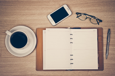surface of a wooden table with notebook, smartphone, eye glasses, and pen photo