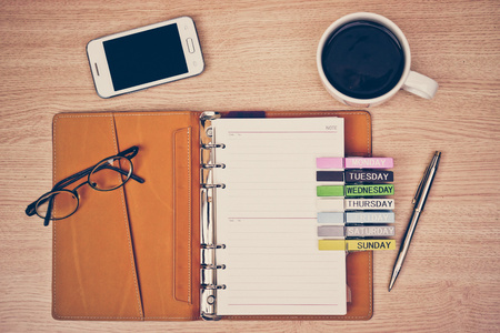 surface of a wooden table with notebook, smartphone, eye glasses, wooden clips with days and pen photo