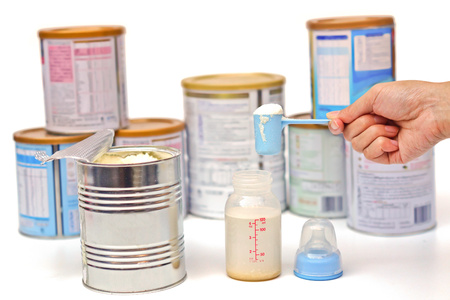 mother preparing powder milk for the baby with different brands of powder milk background
