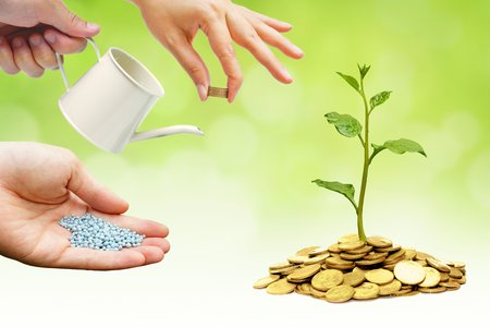 bucket of money: Hands helping planting trees growing on coins together with green background - Building business with csr and ethics