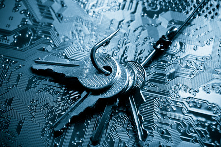 data theft: a fish hook with keys on computer circuit board  phishing  computer data theft concept Stock Photo